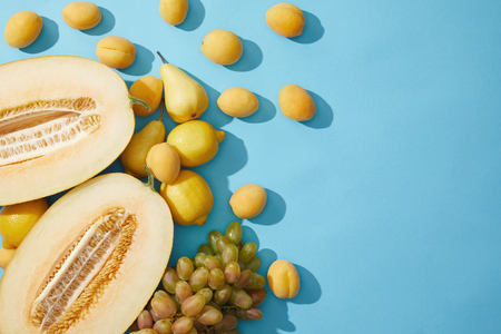 top view of fresh ripe melon, pears, apricots, lemons and grapes on blue background