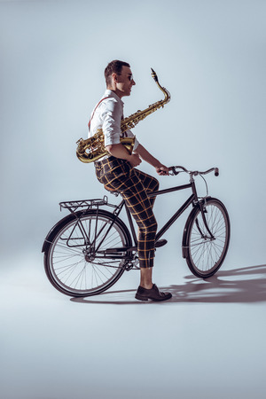 young stylish musician in sunglasses holding saxophone and riding bicycle on grey Stock Photo