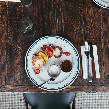 top view of tasty curd pancakes with bowls of dippings and cutlery on wooden table at restaurant