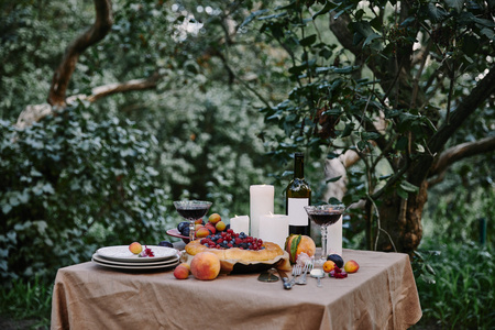 tasty appetizing berries pie, red wine and candles on table in garden