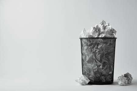 office trash bin with crumpled papers on white surface Stockfoto