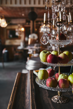 Close-up shot of vintage stand with ripe apples standing on bar counter at restaurant Imagens