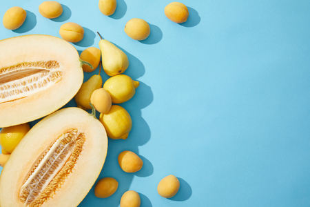 top view of fresh ripe melon, pears, lemons and apricots on blue background
