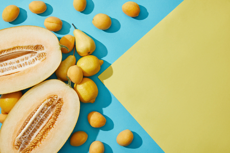 sweet ripe melon, pears, lemons and apricots on yellow and blue background