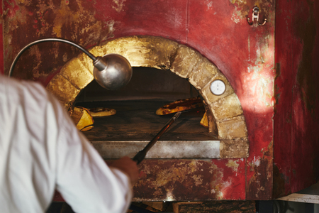 cropped shot of chef taking pizza from masonry oven at restaurant kitchen