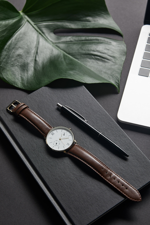 Notebook with pen and watch by laptop on black background 写真素材