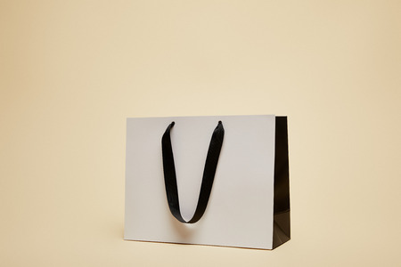 one white shopping bag isolated on beige