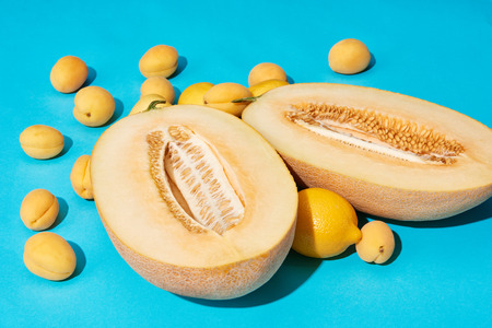 close-up view of ripe sweet halved melon and lemons with apricots on blue