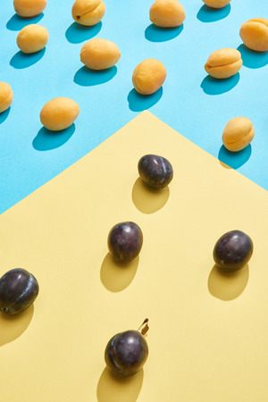 close-up view of fresh sweet plums and apricots on blue and yellow background