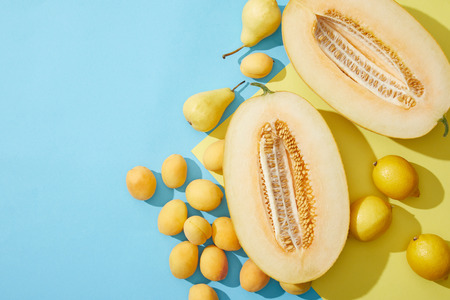 top view of sweet ripe melon, pears, apricots and lemons on blue and yellow background