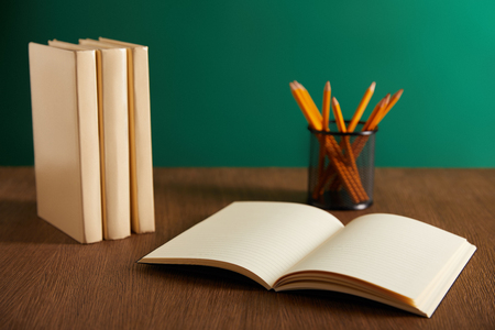 open textbook, books and pencils on wooden table