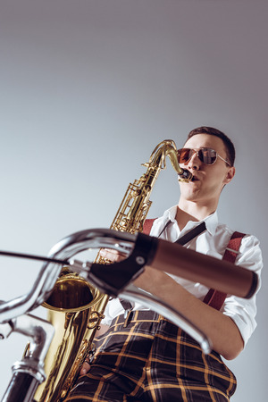 low angle view of stylish young performer in sunglasses playing saxophone on grey