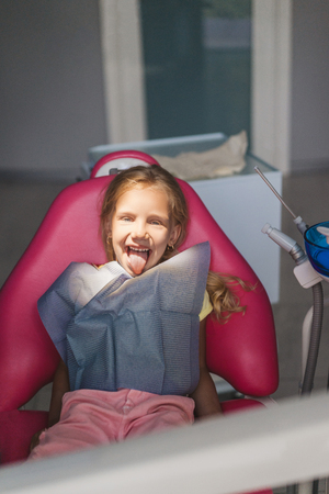 portrait of cute kid sticking tongue out and looking at camera at dentist office