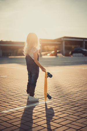 rear view of little kid standing with penny board at parking lot with setting sun behind Фото со стока