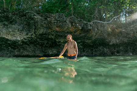 surface level of shirtless smiling male surfer standing in ocean with surfing board in Bali, Indonesia