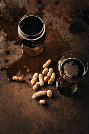 top view of table set with peanuts and mugs of beer on rust surface