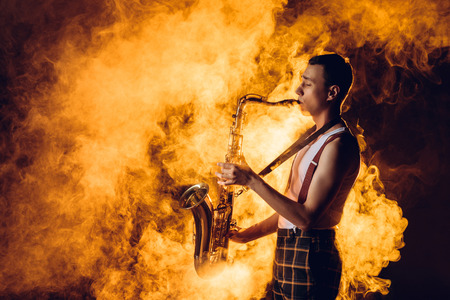 side view of expressive stylish young jazzman playing saxophone in smoke