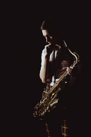 Pensive jeune musicien tenant saxophone isolé sur fond noir