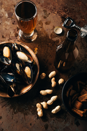 flat lay with beer, baked breads, mussels in bowl and peanuts on rust surface