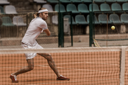focused handsome retro styled man playing tennis at court