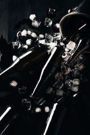 Lay Flat con balde, botellas de vidrio de cerveza y cubitos de hielo dispuestos sobre una mesa oscura