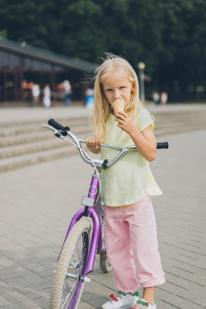 adorable little kid with ice cream and bicycle standing on city street