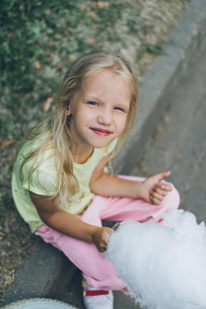 high angle view of smiling child with cotton candy sitting on border 版權商用圖片