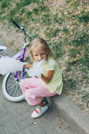 adorable kid with bicycle eating cotton candy in park 版權商用圖片