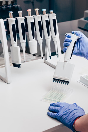 partial view of scientist using multichannel pipette at working table with flasks in modern laboratory