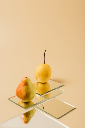 two yellow pears reflecting in mirrors on beige table Фото со стока