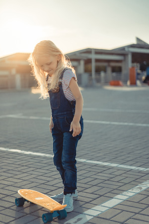 smiling adorable child standing with penny board at parking lot Фото со стока