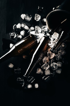flat lay with bucket, glass bottles of beer and ice cubes arranged on dark tabletop Stock Photo