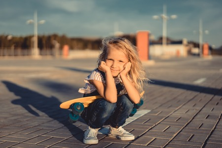 happy adorable child sitting with skateboard and looking at camera at parking lot