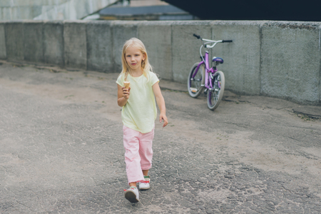 little child with ice cream in hand looking at camera while walking on city street