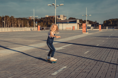 happy little child riding on skateboard at parking lot Фото со стока