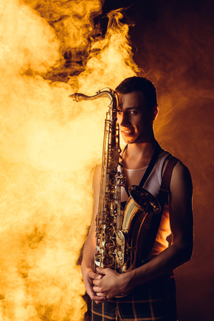 handsome stylish young musician holding saxophone and looking at camera in smoke Stock Photo
