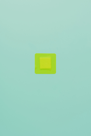 top view of green square adhesive bandage on blue