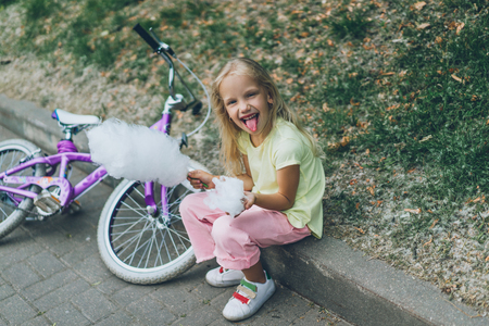 cheerful kid with cotton candy sticking tongue out while sitting on border in park