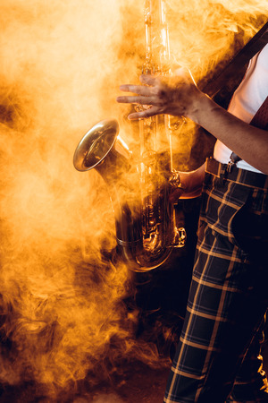 cropped shot of expressive young musician playing saxophone in smoke