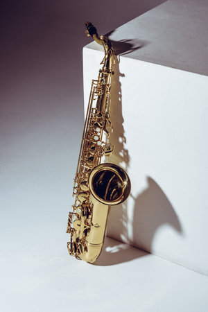 close-up view of single shiny professional saxophone on grey