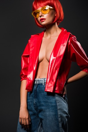 beautiful young woman in short red raincoat on bare skin and vintage eyeglasses isolated on grey