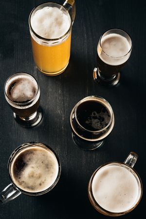 top view of arrangement of glasses of cold beer on dark wooden tabletop 스톡 콘텐츠