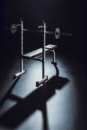 barbell with shadow on floor at gym, black background Reklamní fotografie