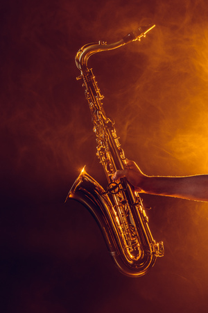close-up partial view of young musician holding saxophone in smoke 写真素材