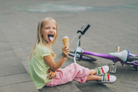cute child with ice cream sticking tongue out while sitting on city steps alone 스톡 콘텐츠