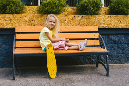 smiling adorable child sitting on bench near skateboard at street