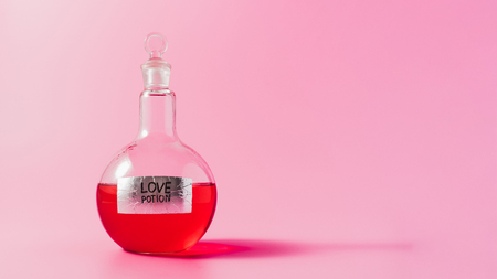close-up shot of flask with red colored love potion on pink surface Stockfoto