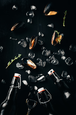 flat lay with bottle opener, bottles of beer, mussels and ice cubes arranged on dark tabletop