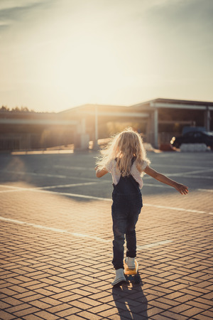 rear view of little kid riding on skateboard at parking lot with setting sun behind