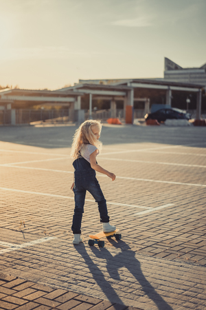 rear view of adorable kid standing with skateboard at parking lot Фото со стока